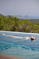A woman floats on her back in an infinity swimming pool.