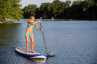 Attractive young woman in bikini on stand up paddle board (SUP) in the beautiful blue waters of Lake Bird Lake, Austin, Texas.