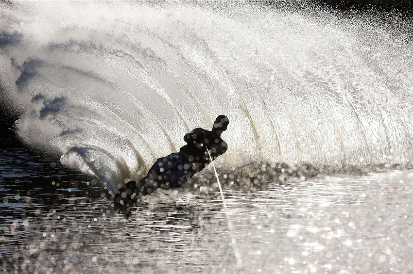 Water skier throws a wall of backlit water and spray in a dramatic afternoon Minnesota lake scene.