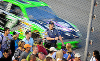 May 2, 2009; Richmond, VA, USA; A police officer works  to keep fans away from the catch fence as NASCAR Sprint Cup Series drivers race by during the Russ Friedman 400 at the Richmond International Raceway. Mandatory Credit: Mark J. Rebilas-