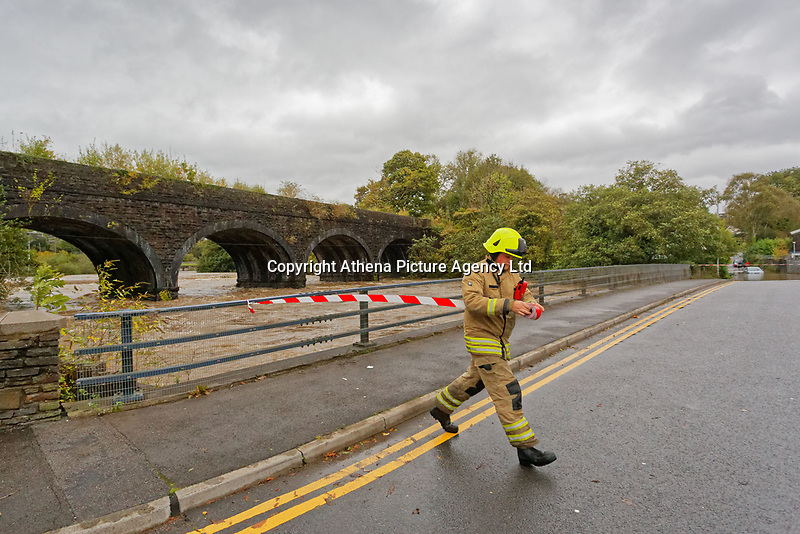 Pictured: A fireman puts a cordon up Dulais Fach Road (B4434) between the areas of Aberdulais and Tonna in Neath, south Wales, UK. Saturday 13 October 2018<br /> Re: Flooding caused by Storm Callum in the Neath area, south Wales, UK.