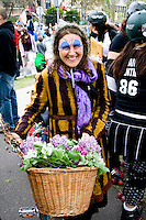 Happy costumed MayDay woman with purple lilacs in bicycle wicker basket. MayDay Parade and Festival. Minneapolis Minnesota USA
