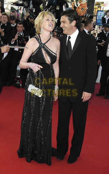 "MELANIE GRIFFITH & ANTONIO BANDERAS.At screening of ""Shrek 2"".Cannes Film Festival, .France 15 May 2004..full length strappyhalterneck one shoulder black sparkly dress holding hands couple married wife husband laughing.Ref: PL.www.capitalpictures.com.sales@capitalpictures.com.©Capital Pictures"