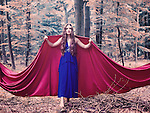 Young woman with brunette hair in blue dress and a red cape standing alone in the forest like a fairytale