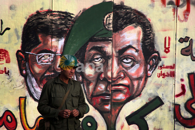 A republican guards soldier stands guard at the presidential palace and anti-Morsi graffiti is seen on the palace's wall behind him in Cairo, Dec. 18, 2012. Egypt's opposition staged rallies across the country on Tuesday to protest against the draft constitution referendum, after the country's Ministry of Justice ordered a probe into allegations of widespread voting irregularities during Saturday's first round of voting on the document. Photo by Ashraf Amra