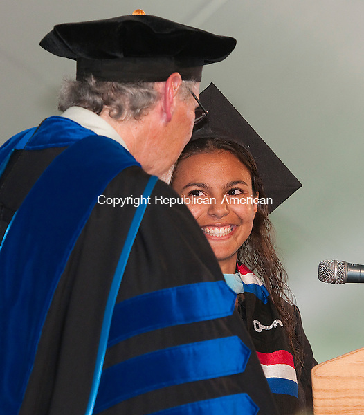 WATERBURY, CT--050915JS08-  Post University's 2015 Senior Class President Eryka Baez, share a laugh with University President Donald Mroz, as she presents the Senior Class Gift during commencement Saturday at Post University in Waterbury. <br /> Jim Shannon Republican-American