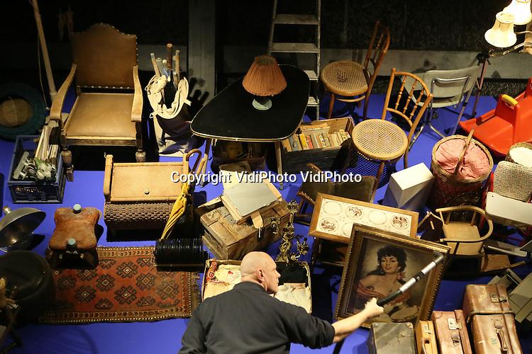 """Foto: VidiPhoto..ARNHEM - Alles aan kant, in het Nederlands Openluchmuseum in Arnhem. De laatste grote schoonmaak. Het stof wordt letterlijk uit alle oude spullen geblazen en gepoetst en de laatste hand wordt gelegd aan nieuwe verzamelingen of collecties. Het museum opent op 29 maart 2013 weer de deuren voor het publiek. Dit jaar is het thema """"Beleef het Weer"""" over de invloed van seizoenen op ons dagelijks leven. Foto: Medewerkers van het Openluchtmuseum zijn bezig met de grote schoonmaak in Spaarstation Dingenliefde. Eén familie, drie generaties, een huis vol bewaarde spullen, samengevat op een verticale wand in een tentoonstelling over sparen, bewaren en verzamelen.."""