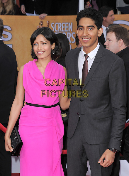 Freida Pinto (wearing Roland Mouret) & Dev Patel.Arrivals at the 19th Annual Screen Actors Guild Awards at the Shrine Auditorium in Los Angeles, California, USA..27th January 2013.SAG SAGs half length pink sleeveless dress black belt clutch bag suit grey gray couple.CAP/DVS.©DVS/Capital Pictures.