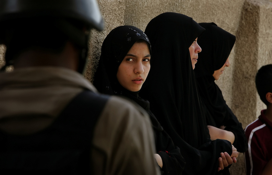 A young Iraqi Sunni woman warily eyes the Iraqi National Policemen searching her family's home in the Baghdad Sunni neighborhood of Ghazaliyah  on Friday August 18, 2006.  The search was part of an operation by bolstered US and Iraqi forces - labelled Operation Together Forward - in response to the extraordinary numbers of sectarian killings in Baghdad.
