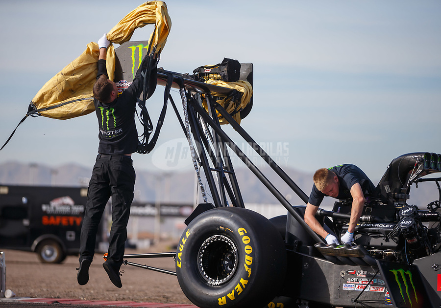 Feb 2, 2018; Chandler, AZ, USA; A crew member for NHRA top fuel driver Brittany Force jumps up to wrap the dragsters parachute around the rear wing during Nitro Spring Training pre season testing at Wild Horse Pass Motorsports Park. Mandatory Credit: Mark J. Rebilas-USA TODAY Sports