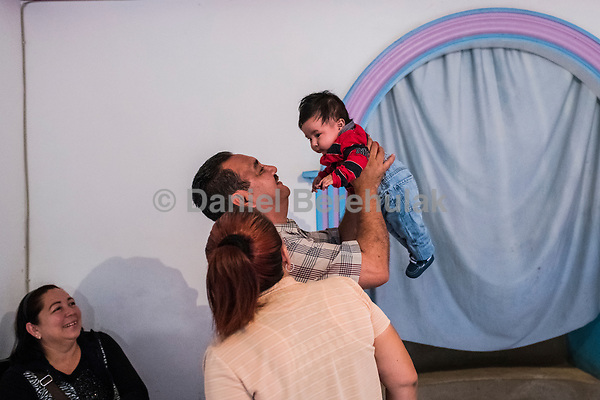 Carlos Saldana, holds his grandson Vicente, 4 months, as Carlos' sister María Isabel Saldaña Grajales and Vicky Delgadillo looks on during a birthday party for their grandson, Hector Yael, 10, at a family gathering at Vicky's daughter, Cinthia Hernández Delgadilo's house in Xalapa, Mexico on November 4, 2017. <br /> Photo Daniel Berehulak for The New York Times