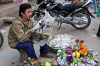 Kathmandu, Nepal.  Nepali Vendor of Flowers and Flower Seeds Reading Newspaper, Downtown Sidewalk Market.