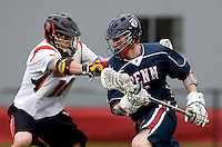 Dean Hart (16) of Maryland checks Chris Harms (6) of Penn behind the goal at Ludwig Field in College Park, Maryland.