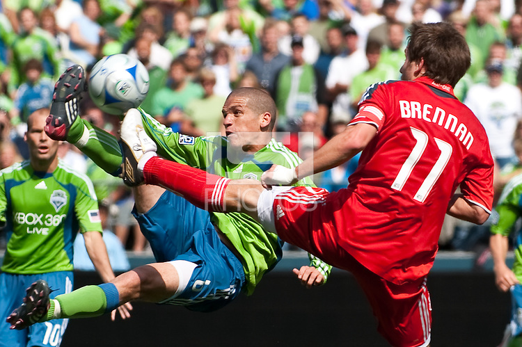 Osvaldo Alonso (L) of the Seattle Sounders makes a specatcular shot against Jim Brennan (11) of Toronto FC in the match at the XBox Pitch at Quest Field on August 29, 2009. The Sounders and Toronto played to a 0-0 draw.