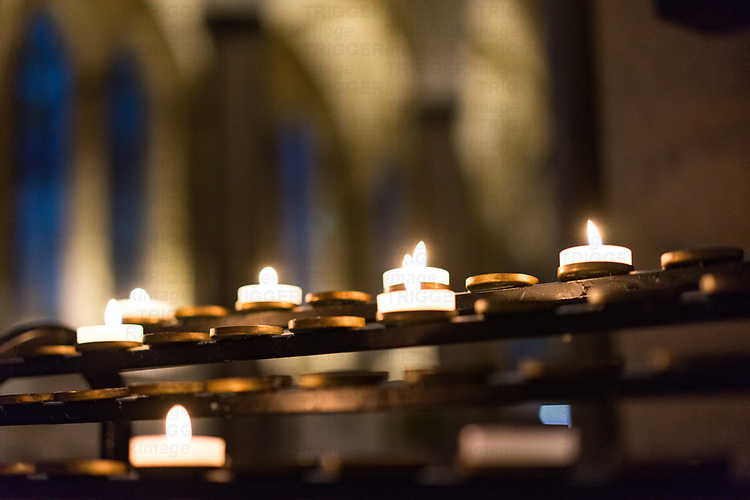 Small candles burning in a Cathedral in England