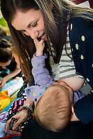 "A mother breastfeeding her baby at a drop-in breastfeeding support centre. The baby is playing with the mother's mouth.<br /> <br /> Image from the ""We Do It In Public"" documentary photography project collection: <br />  www.breastfeedinginpublic.co.uk<br /> <br /> Dorset, England, UK<br /> 17/04/2013"