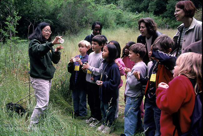 Berkeley CA Park ranger instructing 1st graders and volunteer parents about insect specimen during class field trip to local regional park