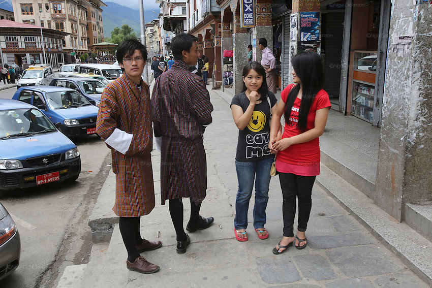 Young men in traditional dress 'Ghos' talk with girls dressed in western clothes. Street scene in Thimpu Bhutan's capital..Bhutan the country that prides itself on the development of 'Gross National Happiness' rather than GNP. This attitude pervades education, government, proclamations by royalty and politicians alike, and in the daily life of Bhutanese people. Strong adherence and respect for a royal family and Buddhism, mean the people generally follow what they are told and taught. There are of course contradictions between the modern and tradional world more often seen in urban rather than rural contexts. Phallic images of huge penises adorn the traditional homes, surrounded by animal spirits; Gross National Penis. Slow development, and fending off the modern world, television only introduced ten years ago, the lack of intrusive tourism, as tourists need to pay a daily minimum entry of $250, ecotourism for the rich, leaves a relatively unworldly populace, but with very high literacy, good health service and payments to peasants to not kill wild animals, or misuse forest, enables sustainable development and protects the country's natural heritage. Whilst various hydro-electric schemes, cash crops including apples, pull in import revenue, and Bhutan is helped with aid from the international community. Its population is only a meagre 700,000. Indian and Nepalese workers carry out the menial road and construction work.