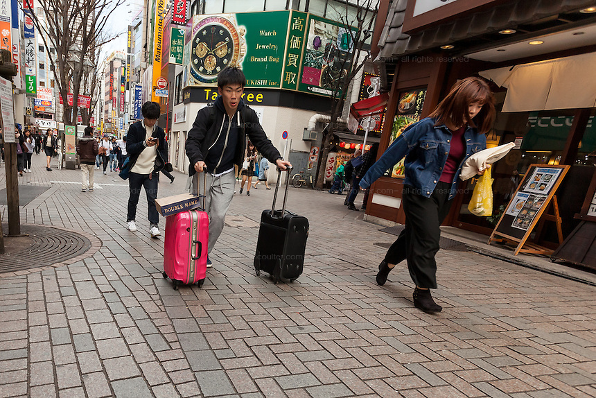 Tourists run with wheeled suitcases in Kabukicho, Shinjuku, Tokyo, Japan. Friday February 17th 2017