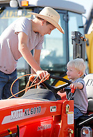 NWA Democrat-Gazette/DAVID GOTTSCHALK  Kelton Center (right) and his brother Range, 2, of Winslow, look over a Kioti KL 6010 tractor Wednesday, September 2, 2015 on the Washington County Fair Grounds in Fayetteville. The Washington County Fair runs through September 5.