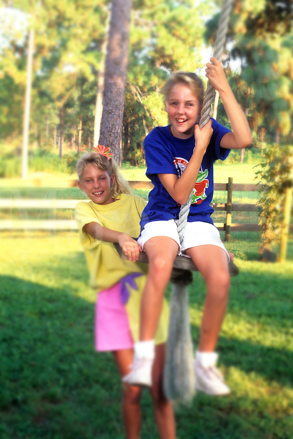 Sisters age 7 and 9 on rope swing in back yard having fun togethe