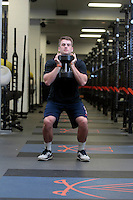 Assistant UVa strength and conditioning coach   Steven Cuccia demonstrates the goblet squat exercise at the McCue Center weight room on campus at the University of Virginia in Charlottesville, VA. Photo/Andrew Shurtleff