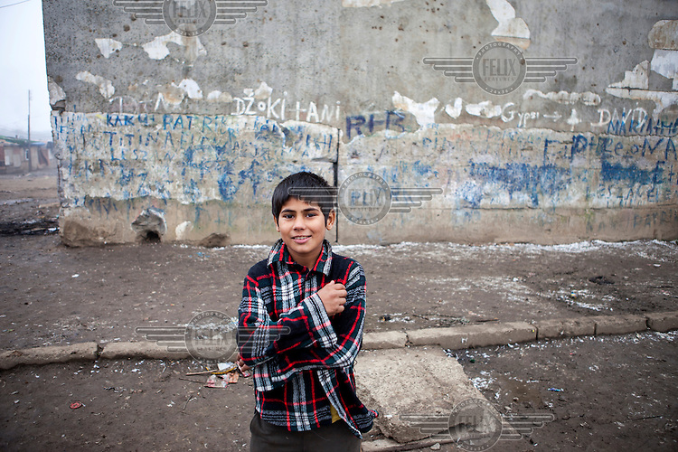 A boy stands in front of a wall in the Roma settlement in 'Budulovskej Street'..