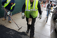 John Mullaney (left), temporary supervisor for construction for the Boston Public Works Department, and David Dollosa repair a sidewalk with asphalt while working for the Boston Public Works Department in Boston, Massachusetts, USA, on April 12, 2012. The city uses a computer system to track public complaints and record work done by city crews to mitigate these complaints.  A supervisor or inspector photographs before and after pictures of the work in addition to making notes about the work done.