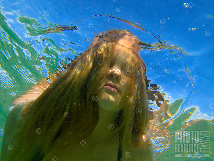 A young girl holds her breath as she comes up for air at Mahai'ula Beach, Big Island.