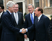 United States President George W. Bush, right center, and his father, former U.S. President George H.W. Bush, left center, look on as Prime Minister Silvio Berlusconi of Italy, right, and former U.S. President Bill Clinton, left, shake hands Thursday, April 7, 2005, prior to dinner at the Prime Minister's Rome residence. The visit came on the eve of Friday's funeral for Pope John Paul II.  .Mandatory Credit: Eric Draper / White House via CNP