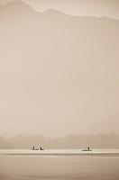 Toned black and white photograph of traditional Kashmiri shikaras and paddlers at sunrise, Dal Lake, Srinagar, Kashmir, India.