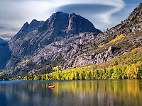 Silver Lake reflection with fall colored cottonwood trees and  boat with fisherman at sunrise.California