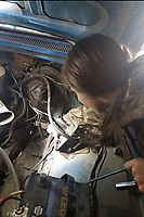 COURTESY PHOTO/Paige leans under the hood to reach and replace the fuse panel in his antique Dodge truck.