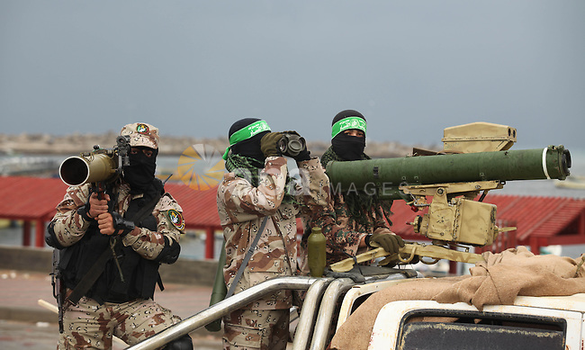 Palestinian members of al-Qassam Brigades, the armed wing of the Hamas movement, display a home-made Qassam rocket during a military parade marking the 27th anniversary of Hamas' founding, in Gaza City December 14, 2014. Photo by Ashraf Amra