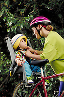 CAUCASIAN MOTHER ADJUSTING CHILD'S BIKE HELMET. MOTHER AND CHILD CYCLISTS. SAN FRANCISCO CALIFORNIA USA.