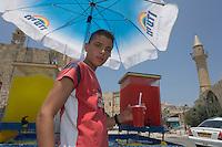 Asie/Israël/Galilée/Saint-Jean-d'Acre: enfant vendant des rafraichissements sur le port devant la vieille ville et sa mosquée
