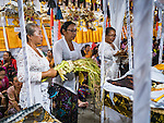 13 JULY 2016 - UBUD, BALI, INDONESIA:  Women bless the effigies of people cremated in the mass cremation in Ubud Wednesday. The effigies will in turn be cremated this weekend. Local people in Ubud exhumed the remains of family members and burned their remains in a mass cremation ceremony Wednesday. Almost 100 people will be cremated and laid to rest in the largest mass cremation in Bali in years this week. Most of the people on Bali are Hindus. Traditional cremations in Bali are very expensive, so communities usually hold one mass cremation approximately every five years. The cremation in Ubud will conclude Saturday, with a large community ceremony.     PHOTO BY JACK KURTZ