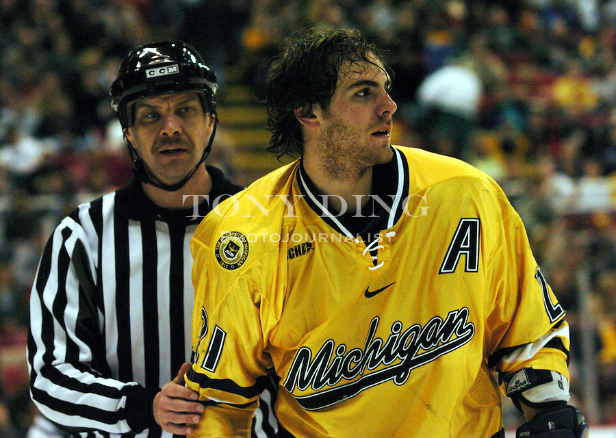 Michigan junior Eric Nystrom (21) is led away from a fight by a referee during the Wolverines' 0-1 loss to Michigan State on Saturday, March 6, 2004 at Joe Louis Arena in Detroit, Michigan. (TONY DING/The Michigan Daily)