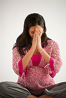 Pregnant Hispanic woman, sitting down, hands praying