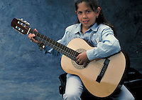 Guitar played by a young Hispanic girl.  May not be used in an elementary school dictionary. Cleveland Ohio USA.