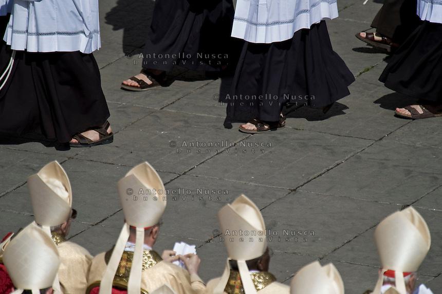 Frati Francescani camminano in Piazza San Pietro osservati da alcuni cardinali durante la celebrazione di una messa.