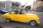 HAVANA - DECEMBER 29: A Cuban man driving a vintage car in front of the capitol building in Havana, Cuba.  Legislation passed in 2011 has legalized car sales to all Cuban citizens who were previously restricted to owning pre-revolution vehicles.
