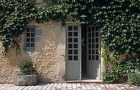 Ivy covers the walls and frames the entrance door of this stone-built country house
