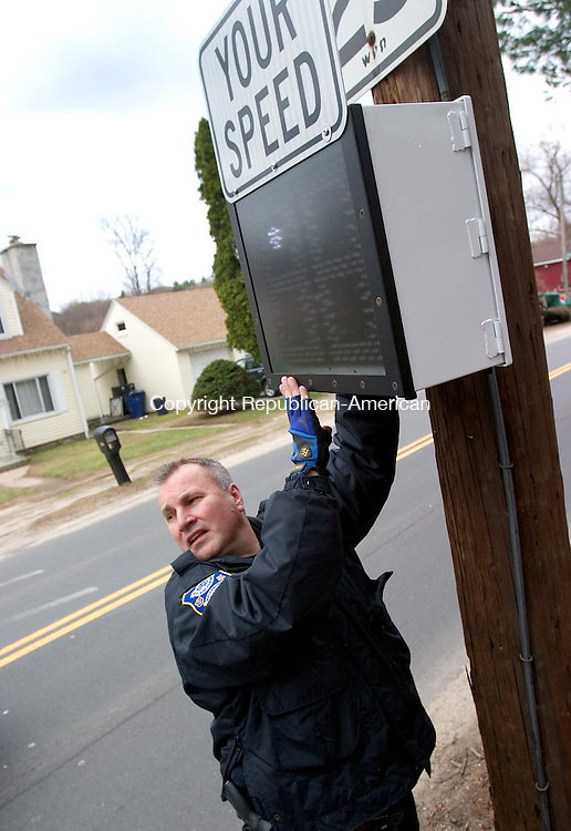 WATERBURY, CT. 24 March 2010-032410SV03-- Police officer Greg LaFountain installs a speed indicator on Perkins Avenue in Waterbury Wednesday. The department received three of these devices through a grant. The device lets drivers know what their actual speed is while traveling the road. The speed indicator also records your speed on a microchip letting police know how fast drivers are traveling the road. LaFountain is part of the community policing program.<br /> Steven Valenti Republican-American