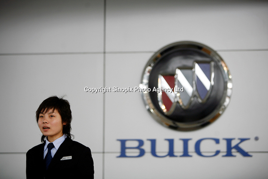 A sales rep stands in front of a Buick logo at a Buick dealership owned and operated by Dongchang Autos in Shanghai, China. Shanghai General Motors (Shanghai GM), Buick's manufacturer in China has just announced a new Chinese market exclusive Buick Park Avenue in the same month. Since 1999 when the Buick Regal was first sold under Shanghai GM, Buick has been one of the most popular automobile brands in China..