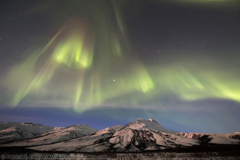 The aurora borealis swirls over the Brooks Range mountains, Arctic, Alaska.