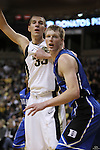 Wake Forest Demon Deacons center Carson Desrosiers (33) looks for the pass with Duke Blue Devils forward Kyle Singler (12) sticking close. Duke leads at halftime 41-32.