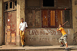 Kids play baseball with a stick and a plastic bottle cap in Havana.