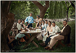 In a backyard enclosed with a picket fence, 10 picnickers (and one pit bull terrier) pause for a toast before their meal. The scene appears casual, but the picnic benches have been angled out from the table to allow each person to be seen, and to lead the eye to the couple serving as host and hostess