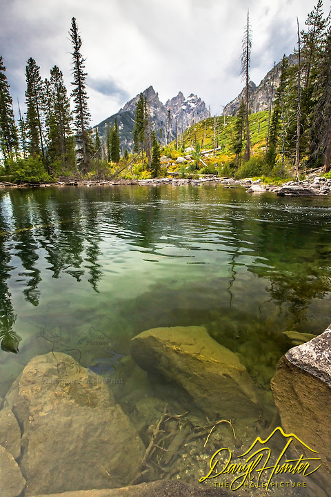 The crystal clear water of Cottonwood Creek in Grand Teton National Park.  The Cathedral Group of the Grand Tetons towers above.